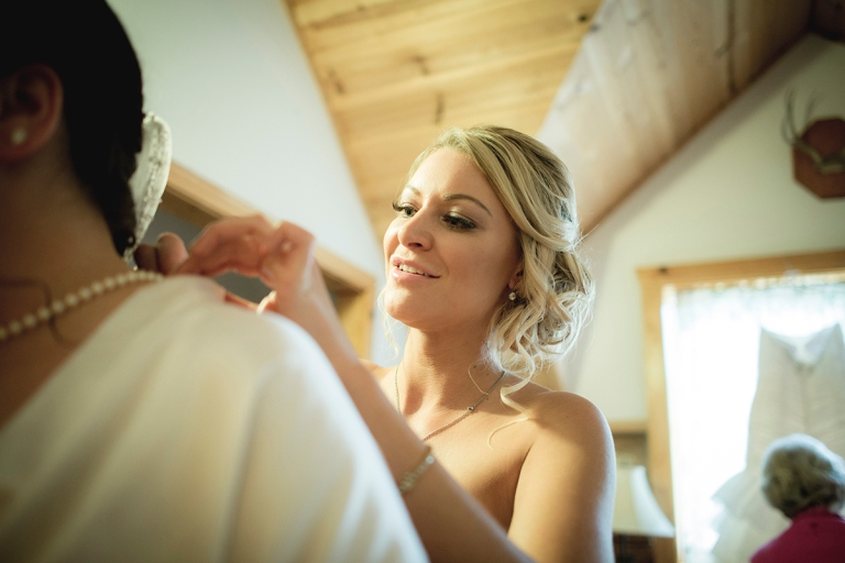 A+J-Bridesmaid-helping-bride-to-close-pearl-neacklace-in-bridal-bedroom-DSC_8019