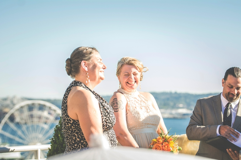 bride laughing with maid of honor during ceremony