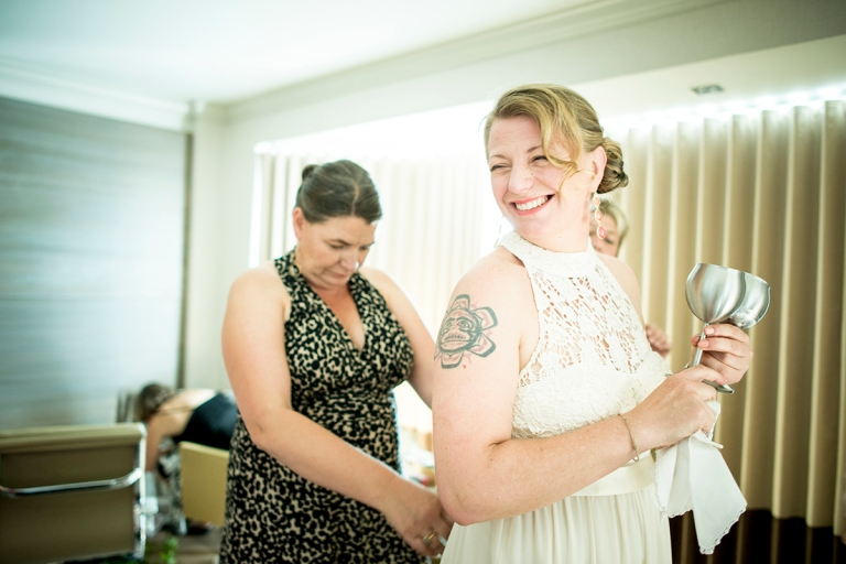 tighting the back of the wedding dress while the bride excited still enjoys her special gift